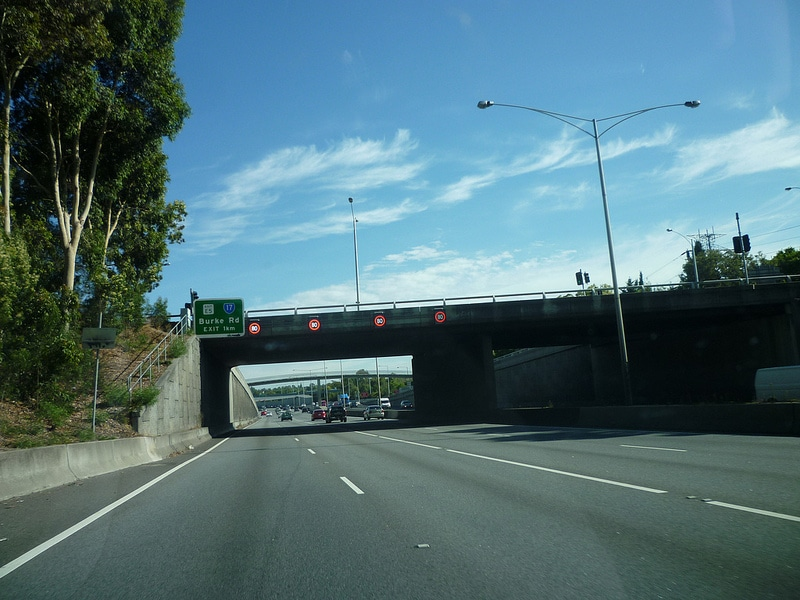 A freeway with Scrolling LED sign in the distance