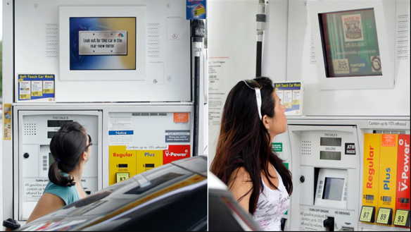 Woman looking up at a gas station LED sign