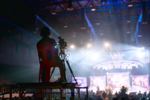 A man filming a concert event with video screens