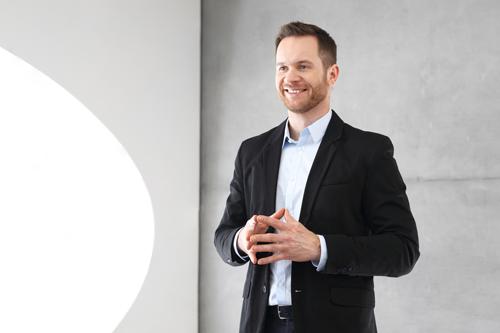 Expert looking man in black suit giving presentation